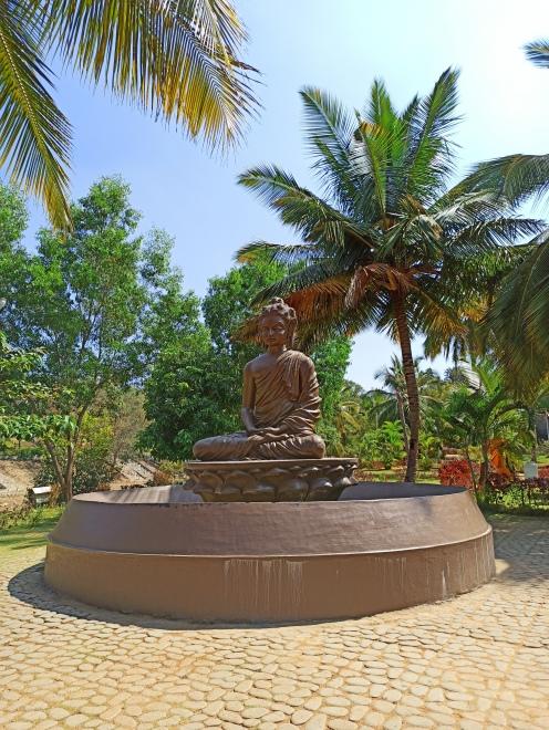 Little Buddha statue infront of pyramid